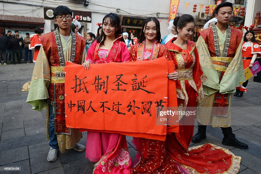 This picture taken on December 24 2014 shows university students wearing traditional Chinese outfits holding banners reading 'Resist Christmas...