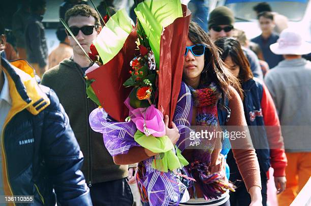 This picture taken on December 25 2011 shows Facebook's founder and billionaire Mark Zuckerberg and his girlfriend Priscilla Chan holding flowers...