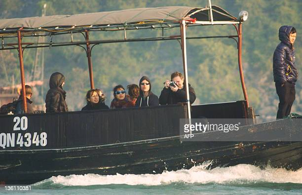 This picture taken on December 25 2011 shows Facebook's founder and billionaire Mark Zuckerberg and his girlfriend Priscilla Chan touring Ha Long Bay...