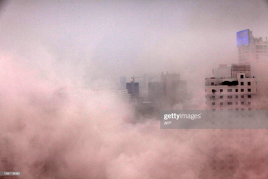 This picture taken on December 25, 2012 shows a plume of dust after a building was demolished in Haikou, south China's Hainan province. For the past two years, China has sought to control residential property prices with measures including restrictions on second and third home purchases, higher minimum downpayments, and annual taxes in some cities on multiple and non-locally-owned homes. CHINA