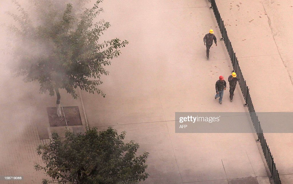 This picture taken on December 25, 2012 shows workers walking through a plume of dust after a building was demolished in Haikou, south China's Hainan province. For the past two years, China has sought to control residential property prices with measures including restrictions on second and third home purchases, higher minimum downpayments, and annual taxes in some cities on multiple and non-locally-owned homes. CHINA