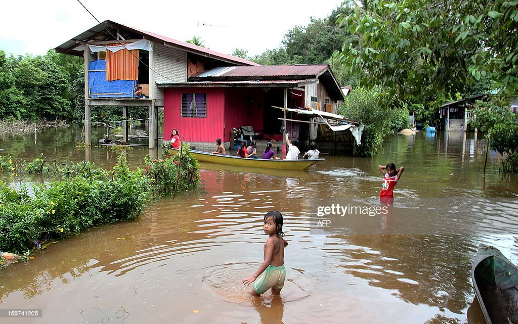 This picture taken on December 26, 2012 shows children playing in flood waters outside their home in Malaysia's northeastern town of Rantau Panjang, boardering Thailand. Floods triggered by torrential monsoon rains in Malaysia have claimed the life of a second victim although waters have subsided, allowing some evacuees to return home from relief centres, reports said. MALAYSIA