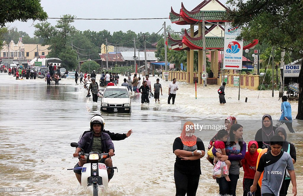 This picture taken on December 26, 2012 shows the residents wade through the flooded streets while shifting to the safer places in Malaysia's northeastern town of Rantau Panjang, boardering Thailand. Floods triggered by torrential monsoon rains in Malaysia have claimed the life of a second victim although waters have subsided, allowing some evacuees to return home from relief centres, reports said. MALAYSIA