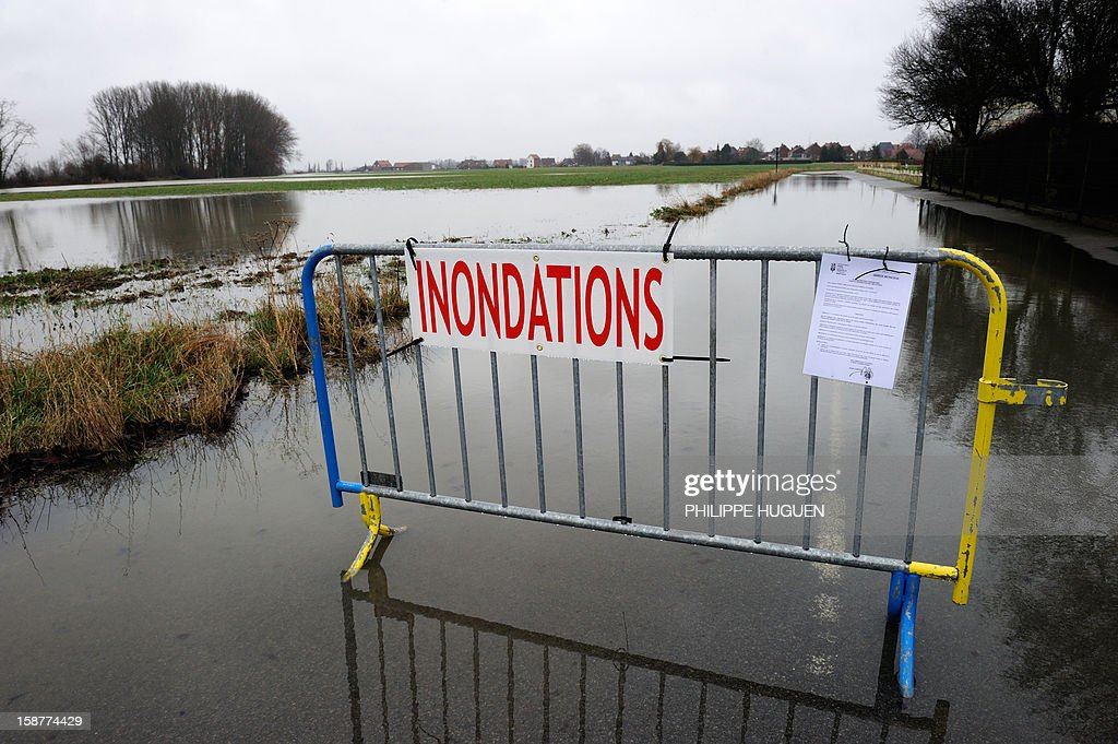 This picture taken on December 28, 2012 shows a sign reading 'Floods' in front of a blocked flooded road after the overflowing of the Lys river caused by recent heavy rainfalls, in Merville, northern France. AFP PHOTO / PHILIPPE HUGUEN