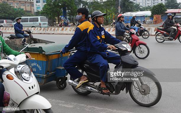 This picture taken on December 3 2014 shows two environmental municipal workers riding on a motorcycle pulling a cart on a street in Hanoi The...