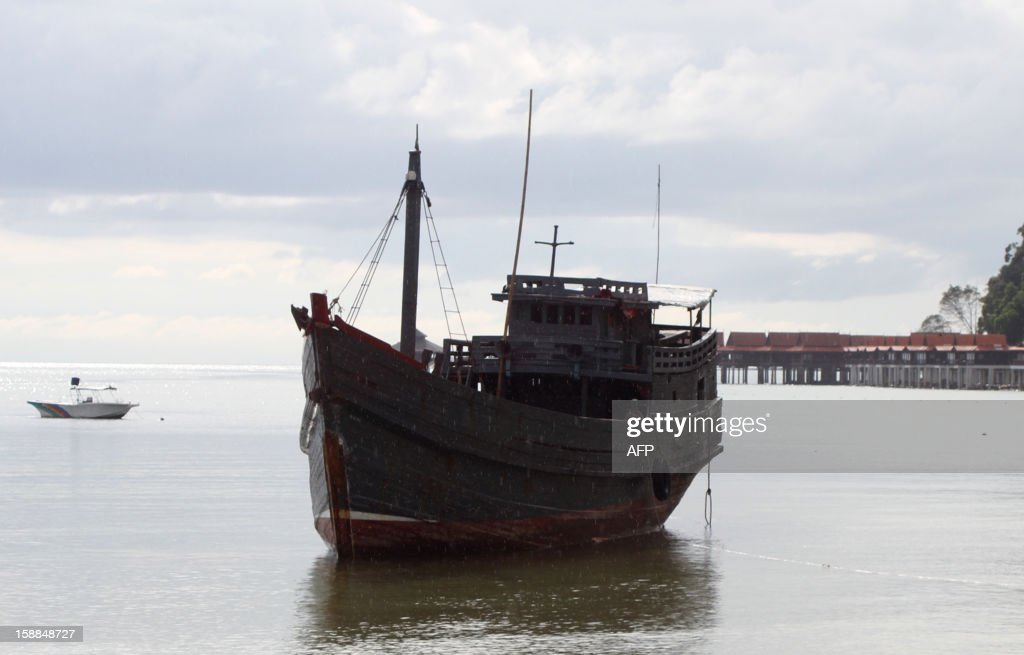 This picture taken on December 30, 2012 shows a boat (C) used by Myanmar Rohingya refugees docked at a beach on Langkawi island, Malaysia's northern Kedah state. About 500 Myanmar nationals swam the last 500 metres to enter Malaysia illegally at the end of a 15-day boat journey at the weekend, leaving one dead, police said on January 1, 2013. MALAYSIA