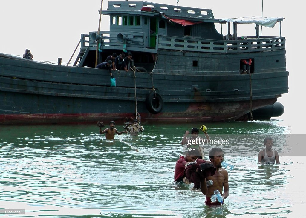 This picture taken on December 30, 2012 shows Myanmar Rohingya refugees disembarking at a beach on Langkawi island, northern Kedah state. About 500 Myanmar nationals swam the last 500 metres to enter Malaysia illegally at the end of a 15-day boat journey at the weekend, leaving one dead, police said on January 1, 2013. MALAYSIA