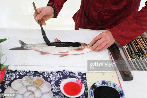 This picture taken on December 4 2014 shows folk artist Han Xiaoming applying paint to a live fish in Hangzhou east China's Zhejiang province Han...