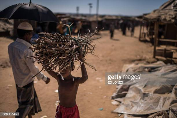 TOPSHOT This picture taken on December 4 2017 shows a young Rohingya refugee carrying firewood as he walks through the Kutupalong refugee camp in...