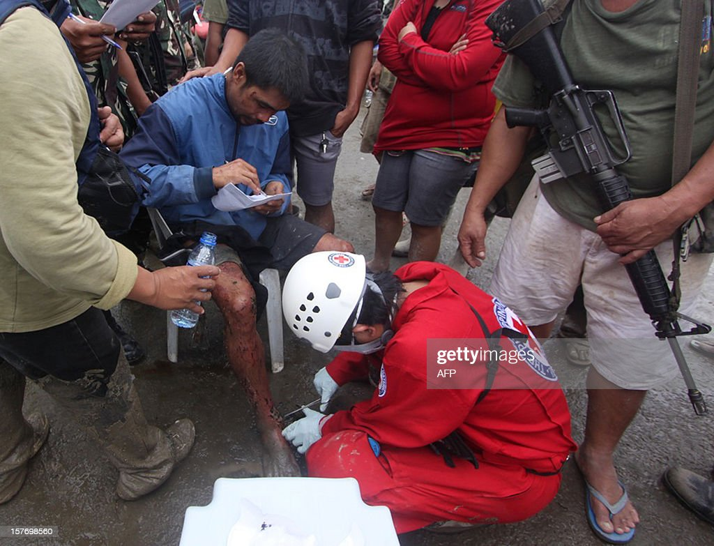 This picture taken on December 5, 2012 shows a Red Cross volunteer (C, bottom) giving first aid to a seated rescued soldier (L) in the aftermath of Typhoon Bopha in New Bataan, Compostela Valley in the southern Philippines on December 5, 2012. At least 325 people were killed and hundreds remain missing in the Philippines following the deadliest typhoon to hit the country this year, the civil defence chief said on December 6. AFP PHOTO / Karlos Manlupig
