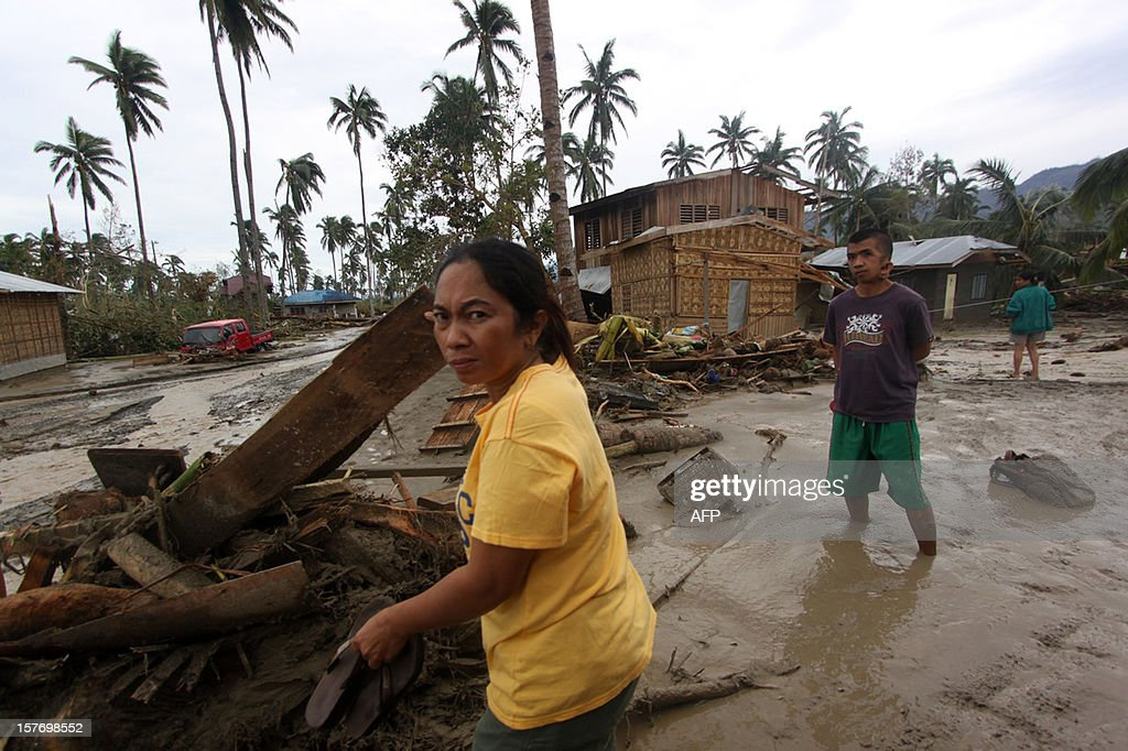 This picture taken on December 5, 2012 shows residents walking along a street covered with mud and debris following Typhoon Bopha in New Bataan, Compostela Valley in the southern Philippines. At least 325 people were killed and hundreds remain missing in the Philippines following the deadliest typhoon to hit the country this year, the civil defence chief said on December 6. AFP PHOTO / Karlos Manlupig