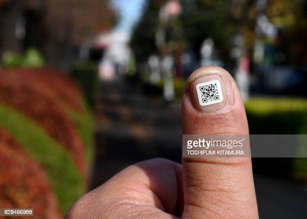 This picture taken on December 5 2016 shows a city officer displaying a QR code on his fingernail near the Iruma city hall in Iruma Saitama...