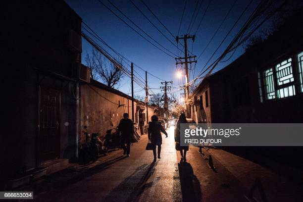 This picture taken on December 5 2016 shows people returning home from work in a hutong in Beijing With space scarce in the city of 215 million most...