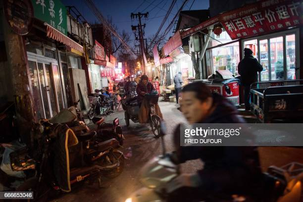 This picture taken on December 5 2016 shows people riding in a hutong in Beijing With space scarce in the city of 215 million most hutong courtyards...