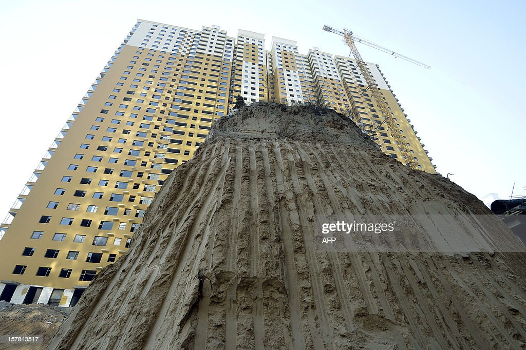 This picture taken on December 6, 2012 shows a grave mound 10 meters high, at a construction site in a village in Taiyuan, north China's Shanxi province . The owner of the grave and the construction consortium are arguing over compensation to be paid. The 'nail grave' as it is being referred to by Asian media outlets, is the latest in a series of acts of resistance against land dispossession from Chinese people. Other examples have seen a freeway constructed around a lone house, and a lone house left standing on a mound in the middle of a construction site. CHINA