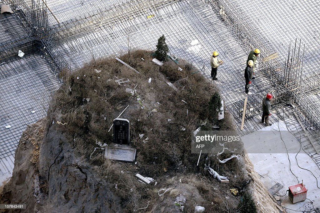 This picture taken on December 6, 2012 shows Chinese workers building around a grave mound (L) which stands 10 meters high, at a construction site in a village in Taiyuan, north China's Shanxi province . The owner of the grave and the construction consortium are arguing over compensation to be paid. The 'nail grave' as it is being referred to by Asian media outlets, is the latest in a series of acts of resistance against land dispossession from Chinese people. Other examples have seen a freeway constructed around a lone house, and a lone house left standing on a mound in the middle of a construction site. CHINA