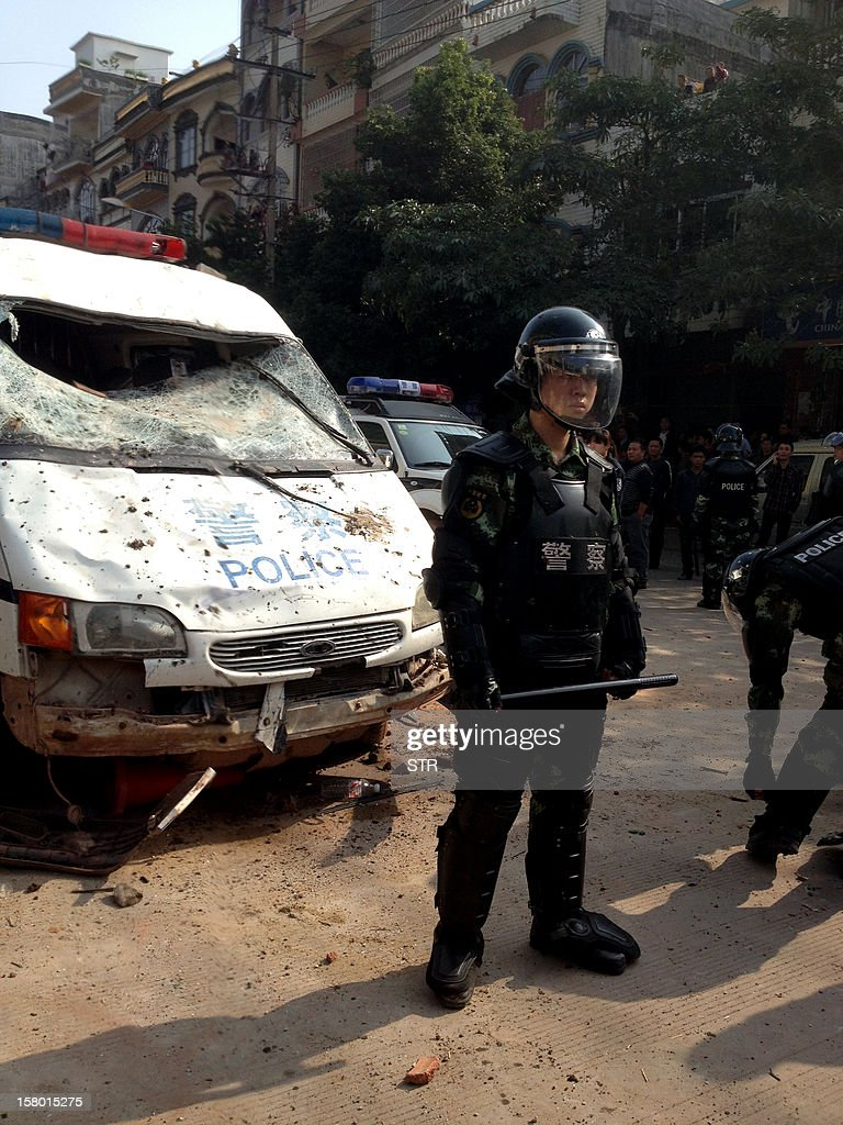 This picture taken on December 7, 2012 shows a Chinese riot policeman standing guard by a damaged police vehicle after rioters destroyed numerous police and border patrol vehicles during a clash with security forces in Dongxing city, southwest China's Guangxi Region. Police in a south China city bordering Vietnam on December 7 clashed with thousands of rioters who were protesting excessive brutality meted out to a suspected smuggler, the government and a rights group said. CHINA