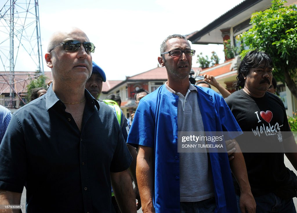 This picture taken on December 7, 2012 shows Italian fugitive mafia boss Antonino Messicati Vitale (2nd R) being escorted by Indonesian police officers and an Italian police officer (front L) in Denpasar on Bali island, following his arrest. Italian police have arrested a fugitive mafia boss living in a luxury home on the island of Bali in a joint operation with Indonesian authorities, police said on December 7. AFP PHOTO/SONNY TUMBELAKA