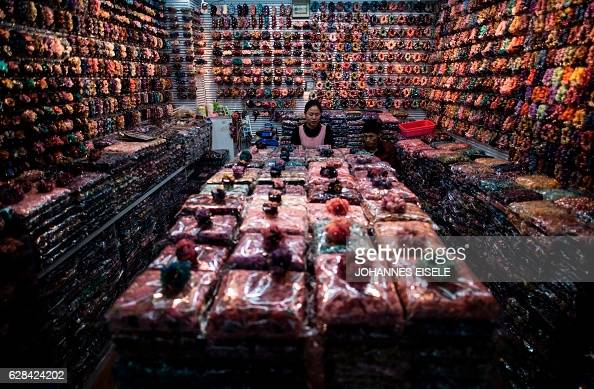 TOPSHOT This picture taken on December 7 2016 shows a vendor sitting in her both at the Yiwu market a wholesale market of general merchandise in Yiwu...