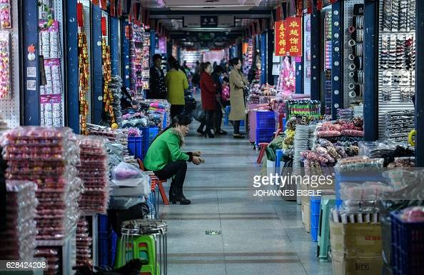 This picture taken on December 7 2016 shows a vendor sitting in her both at the Yiwu market a wholesale market of general merchandise in Yiwu in...