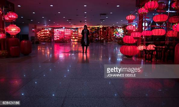 This picture taken on December 7 2016 shows a woman looking at her phone at the Yiwu market a wholesale market of general merchandise in Yiwu in...