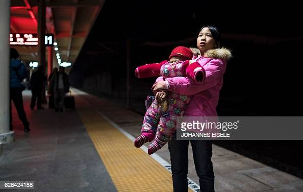 This picture taken on December 7 2016 shows a young girl carrying a baby as they wait for a train with her family in Yiwu in Zhejiang province China...