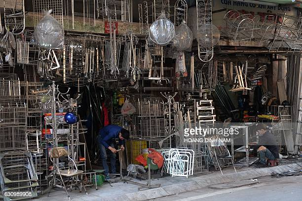 TOPSHOT This picture taken on December 8 2016 shows men working at metal houseware shops on Lo Ren street in downtown Hanoi Sitting before a bright...