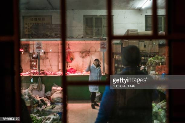 This picture taken on December 8 2016 shows vendors playing badminton in a supermarket as they wait for clients in a hutong in Beijing With space...