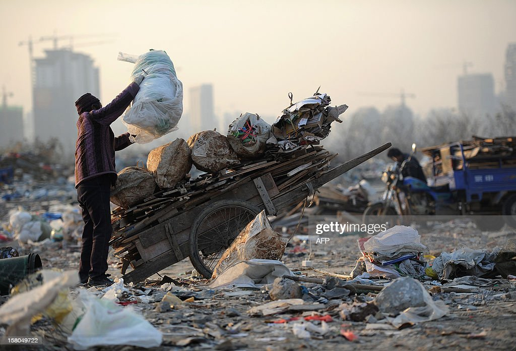 This picture taken on December 9, 2012 shows a female scavenger putting useful construction waste she picked up onto her trolly in a garbage dump in Hefei, central China's Anhui province. China's wealth gap has widened to a level where it is among the world's most unequal nations, a Chinese academic institute said in a survey, as huge numbers of poor are left behind by the economic boom. CHINA