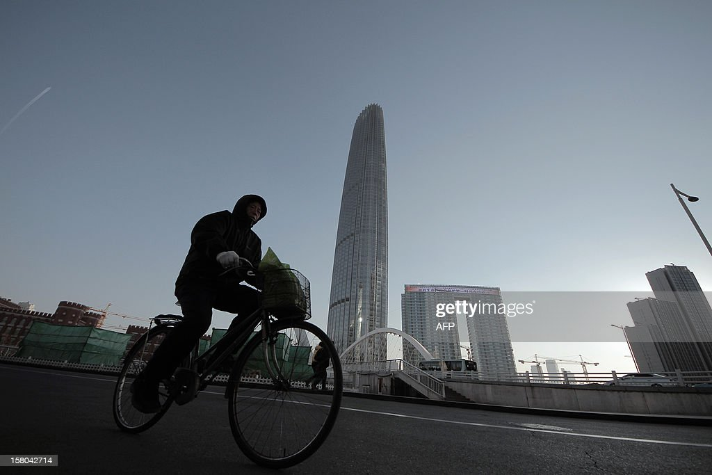 This picture taken on December 9, 2012 shows a man cycling past the highest building in north China's Tianjin. China's monthly trade surplus fell to 19.6 billion USD in November, down 38.6 percent from October, the government said on December 10, as weak overseas demand weighed on the world's second-largest economy. CHINA OUT AFP PHOTO