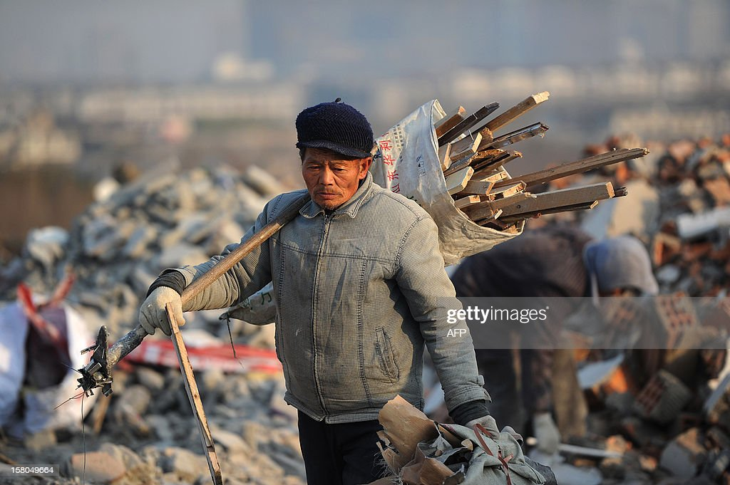 This picture taken on December 9, 2012 shows a scavenger walking in a construction waste garbage dump in Hefei, central China's Anhui province. China's wealth gap has widened to a level where it is among the world's most unequal nations, a Chinese academic institute said in a survey, as huge numbers of poor are left behind by the economic boom. CHINA OUT AFP PHOTO