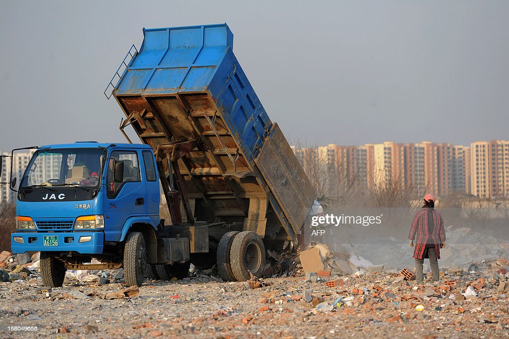 This picture taken on December 9, 2012 shows a scavenger watching a truck unloading construction waste to a garbage dump in Hefei, central China's Anhui province. China's wealth gap has widened to a level where it is among the world's most unequal nations, a Chinese academic institute said in a survey, as huge numbers of poor are left behind by the economic boom. CHINA OUT AFP PHOTO