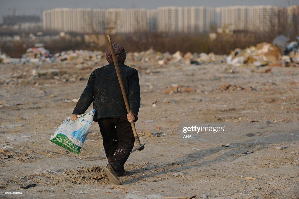 This picture taken on December 9, 2012 shows an elderly scavenger picking up useful construction waste from a garbage dump in Hefei, central China's Anhui province. China's wealth gap has widened to a level where it is among the world's most unequal nations, a Chinese academic institute said in a survey, as huge numbers of poor are left behind by the economic boom. CHINA OUT AFP PHOTO
