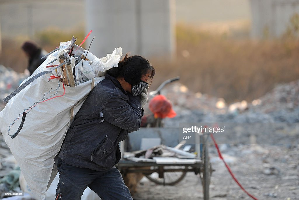 This picture taken on December 9, 2012 shows scavengers picking up usefull construction waste from a garbage dump in Hefei, central China's Anhui province. China's wealth gap has widened to a level where it is among the world's most unequal nations, a Chinese academic institute said in a survey, as huge numbers of poor are left behind by the economic boom. CHINA