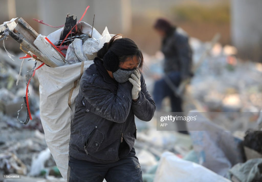 This picture taken on December 9, 2012 shows scavengers picking up usefull construction waste from a garbage dump in Hefei, central China's Anhui province. China's wealth gap has widened to a level where it is among the world's most unequal nations, a Chinese academic institute said in a survey, as huge numbers of poor are left behind by the economic boom. CHINA OUT AFP PHOTO