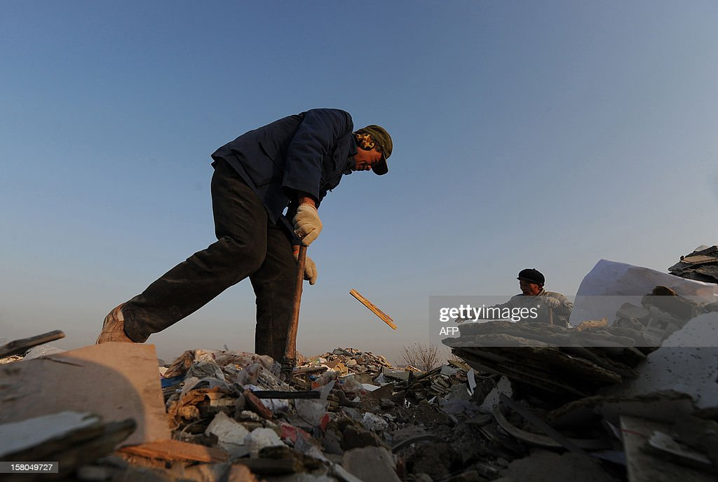 This picture taken on December 9, 2012 shows scavengers picking up useful construction waste from a garbage dump in Hefei, central China's Anhui province. China's wealth gap has widened to a level where it is among the world's most unequal nations, a Chinese academic institute said in a survey, as huge numbers of poor are left behind by the economic boom. CHINA OUT AFP PHOTO