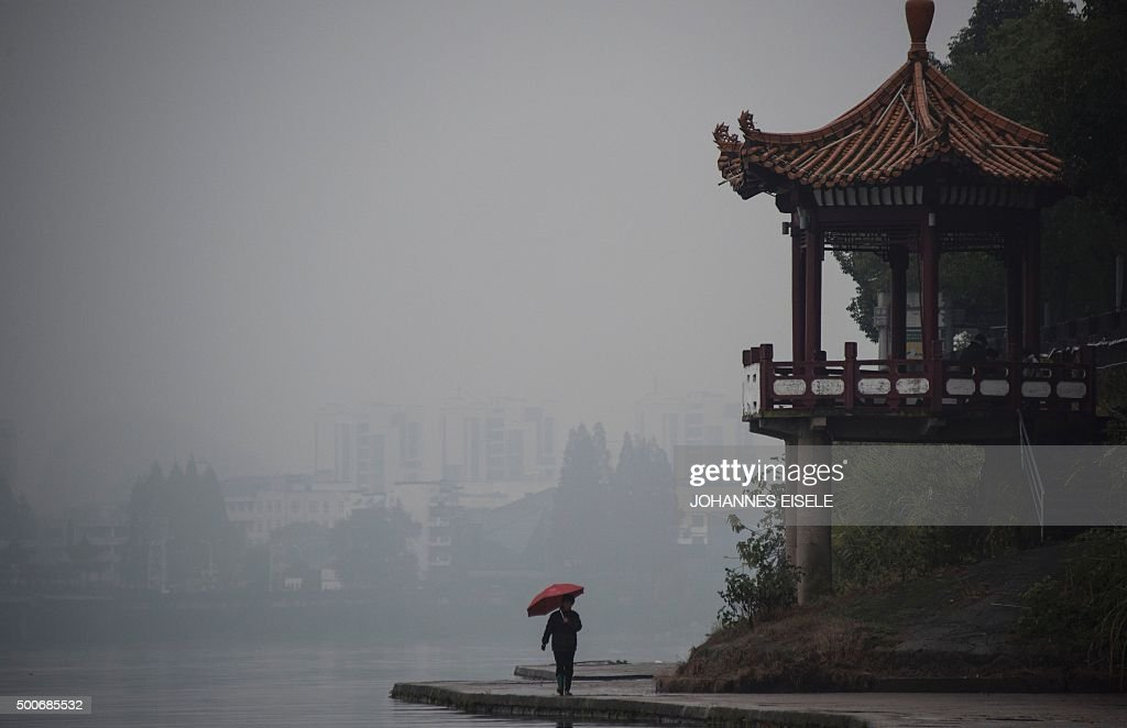 TOPSHOT This picture taken on December 9 2015 shows a woman walking with her umbrella next to the Xin'an River on a rainy day in Huangshan city...