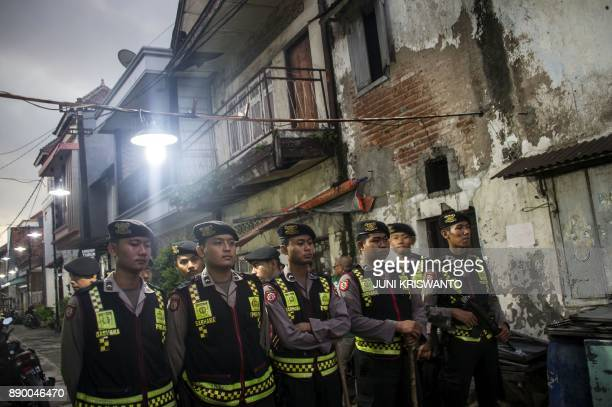 This picture taken on December 9 2017 shows Indonesian policemen standing guard while antiterror policemen conduct a raid in Surabaya More than a...