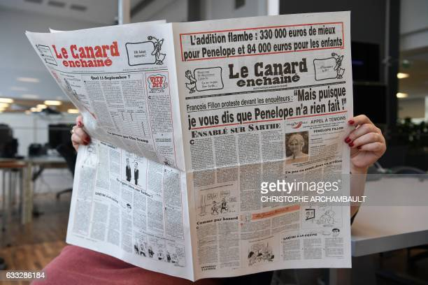This picture taken on February 1 2017 in Paris shows a journalist reading the February 1 2017 issue of French satirical newspaper 'Le Canard...