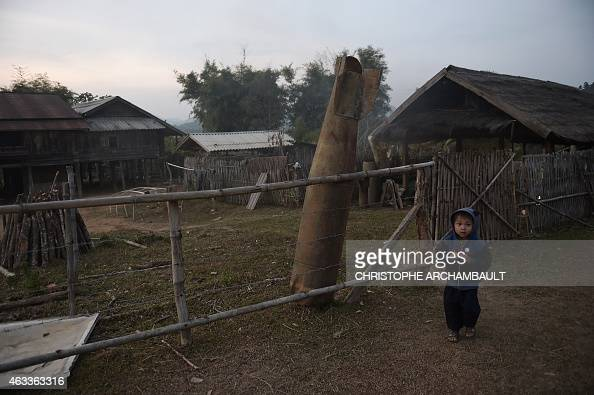 This picture taken on February 10 2015 shows a Laotian boy walking past a Vietnam War bomb shell standing against the fence of a house in Ban Napia...