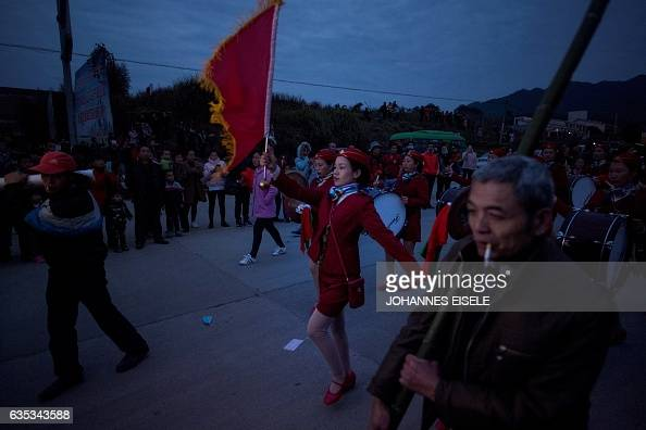 This picture taken on February 11 2017 shows members of a marching band leading villagers during a dragon parade in Gutian village Liancheng county...