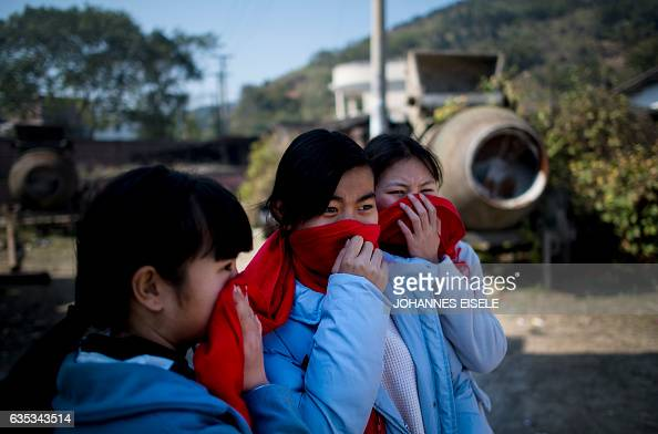 This picture taken on February 11 2017 shows three girls using a red scarf to protect themselves against smoke as the dragon is burned as an offering...