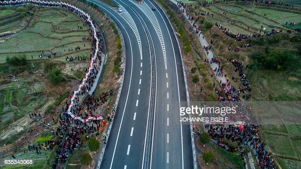 TOPSHOT This picture taken on February 11 2017 shows villagers parading a dragon through a tunnel next to a highway in the fields near Gutian village...