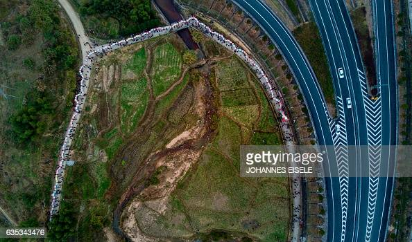 TOPSHOT This picture taken on February 11 2017 shows villagers parading a dragon next to a highway in the fields near Gutian village Liancheng county...