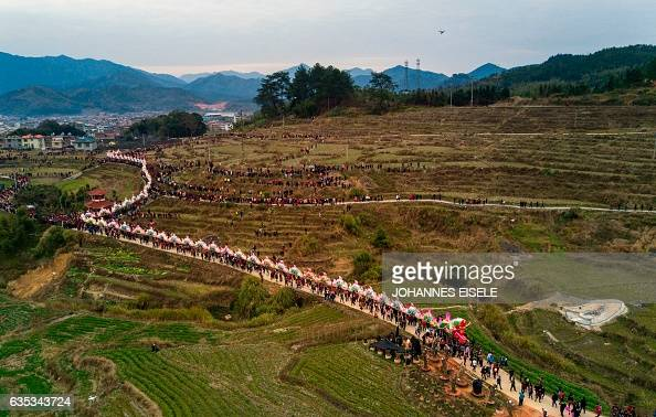 TOPSHOT This picture taken on February 11 2017 shows villagers parading a dragon through fields near Gutian village Liancheng county of China's...