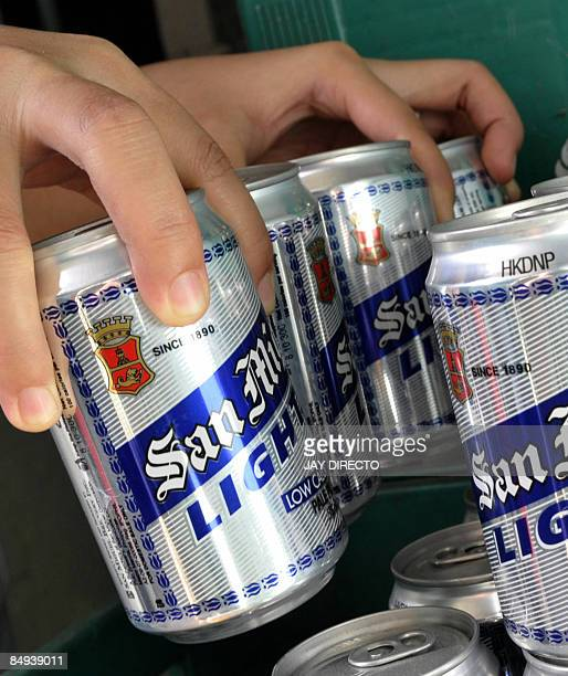 This picture taken on February 12 2009 shows a worker stocking San Miguel beer cans at a bar in Manila Japan's Kirin Holdings said on Februar 20 2009...
