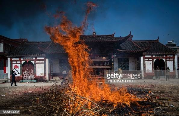 This picture taken on February 12 2017 shows the fire after a dragon was burned as an offering after a parade in Gutian village Liancheng county of...
