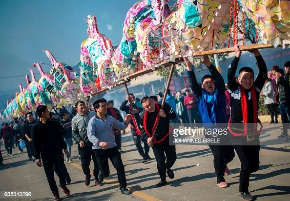 TOPSHOT This picture taken on February 12 2017 shows villagers parading a dragon before burning it as an offering in Gutian village Liancheng county...