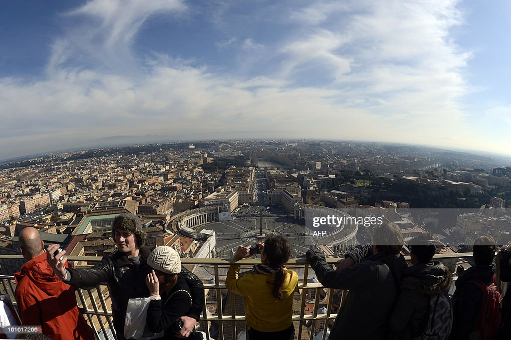 This picture taken on February 13, 2013 at the Vatican shows tourists standing on the dome of St Peter's basilica and a view of St Peter's square.