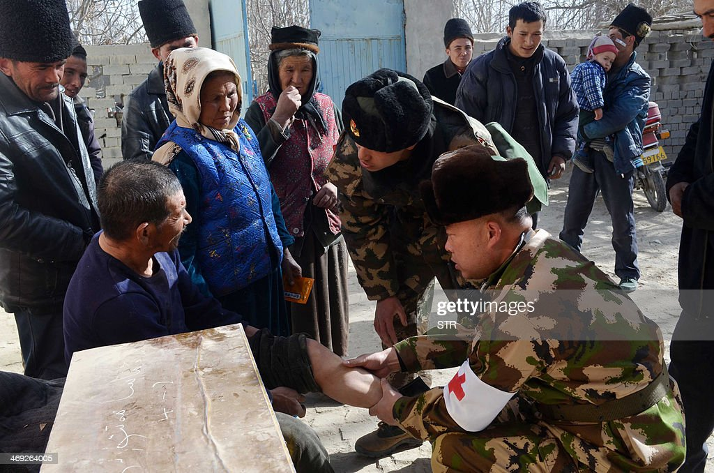 This picture taken on February 13, 2014 shows Chinese rescuers providing medical attention to villagers in Hotan, farwest China's Xinjiang region. A strong and shallow 6.8-magnitude earthquake struck China's far western region of Xinjiang on February 12, but in a sparsely populated area, the US Geological Survey said. CHINA OUT AFP PHOTO